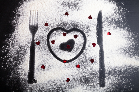 Silhouettes of fork, knife and hearts on the flour on a black background.