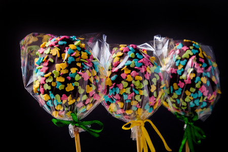 kiss biscuits: Homemade tiny cakes - cake pops in egg shape on a dark background. Easter theme. Toned.