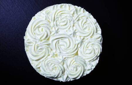 topper: Homemade cake with creamy decor on a black background. Toned.