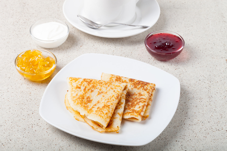 blini: Cup of tea with jam, sour cream and russian pancakes - blini. Stock Photo