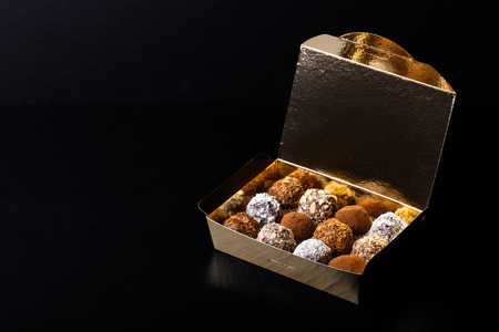 Set of different kinds of homemade chocolate truffles in a golden box. Stock Photo