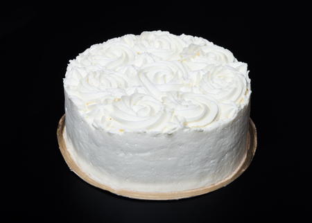 Homemade cake with creamy decor on a black background.