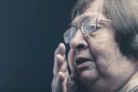 grayness: Portrait of elderly woman. Secret. Toned.