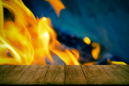 View from wooden table to bright flame of bonfire. Collage. Defocused. Toned.