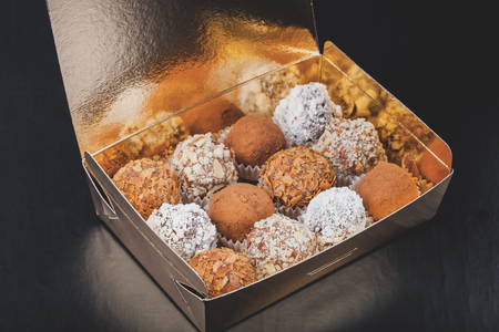 Set of different kinds of homemade chocolate truffles in a golden box. Toned. Stock Photo