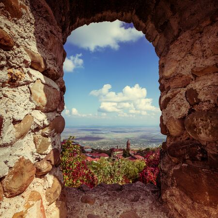 Beautiful autumn mountain landscape in Kakheti view through the loophole in an ancient stone wall. Georgia. Toned. Stock Photo