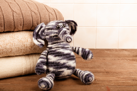 Knitted toy elephant with the stack of knitted clothes on wooden table opposite a light tile wall. Toned.