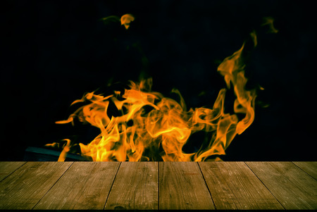 View from wooden table to bright flame of bonfire.