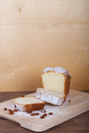 Slices of curd cake with sugar powder on the wooden cutting board. Selective focus.