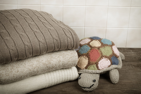 beige: Knitted toy turtle with the stack of knitted clothes on wooden table opposite a light tile wall. Toned.