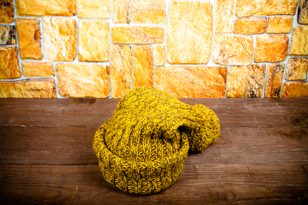 Handmade knitted hat on a dark wooden table opposite stone wall. Toned. Stock Photo