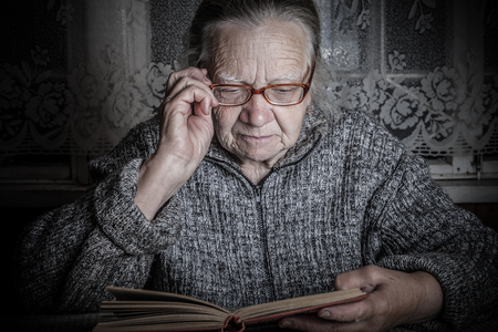 grayness: Elderly woman reads book in rustic interior. Toned. Stock Photo