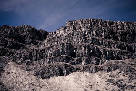 cascade: Stony hill on the shore of the fjord in eastern Iceland. Toned. Stock Photo