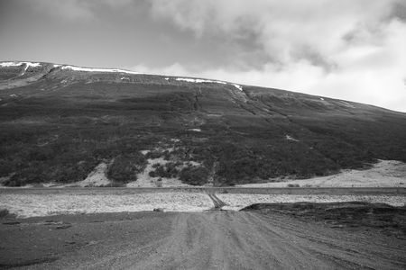 cascade: Gravel road on the beautiful landscape in the east of Iceland. Toned.