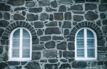 Window on the wall of natural stones of traditional Iceland house for background. Toned.