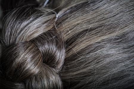 grayness: The hair of an elderly woman is gathered at the back of the head. Close up detail. Toned.