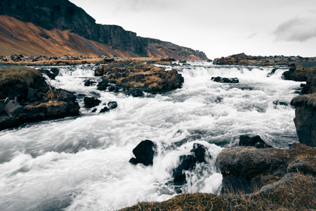 Stormy mountain river in the severe stony deserted landscape of Iceland. Toned.