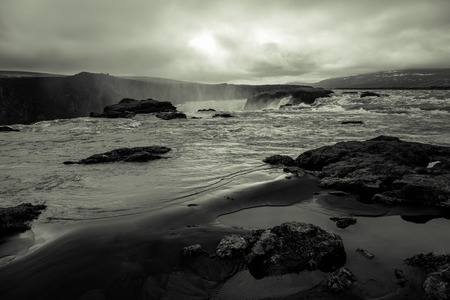 cascade: Water of the Godafoss Waterfall - beautiful part of stony rocky desert landscape of Iceland. Toned.