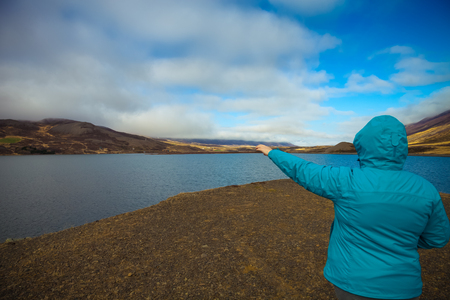 Woman in a blue jacket with her back to the photographer on the coast of huge cold lake on the stony rocky desert landscape of Iceland. Toned.