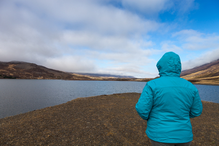 Woman in a blue jacket with her back to the photographer on the coast of huge cold lake on the stony rocky desert landscape of Iceland.