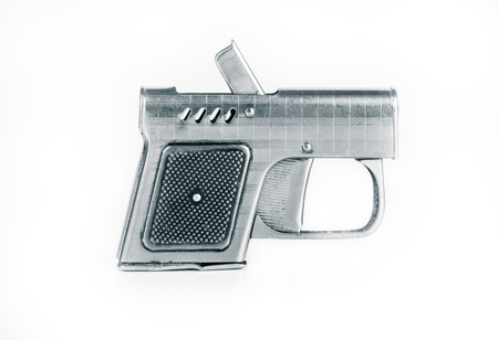 gas lighter: Lighter in the form of a gun on a light background. Toned. Stock Photo
