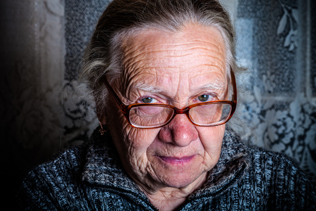 grayness: Elderly woman with glasses in rustic interior. Toned. Stock Photo