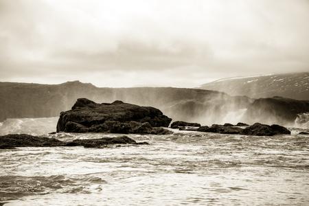 jet stream: Water of the Godafoss Waterfall - beautiful part of stony rocky desert landscape of Iceland. Toned.