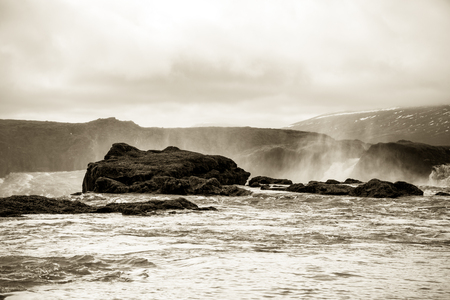 Water of the Godafoss Waterfall - beautiful part of stony rocky desert landscape of Iceland. Toned.