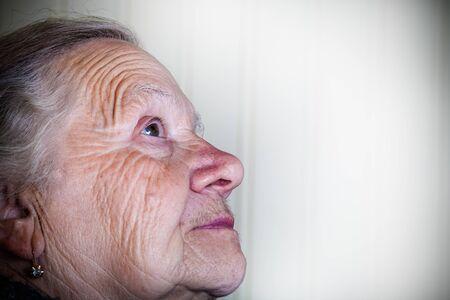 Portrait of an elderly woman on a light background. Thoughtful profile. Toned. Lizenzfreie Bilder