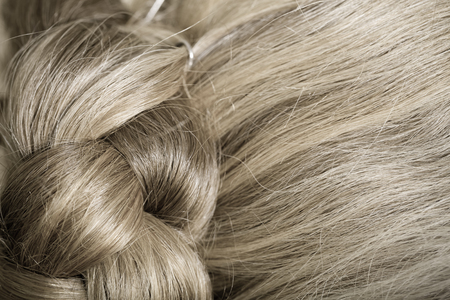 The hair of an elderly woman is gathered at the back of the head. Close up detail. Toned.