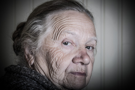 grayness: Portrait of an elderly woman on a light background. Thoughtful profile. Toned. Stock Photo