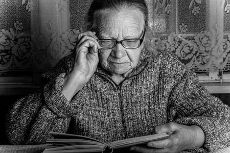 Elderly woman reads book in rustic interior. Toned. Lizenzfreie Bilder