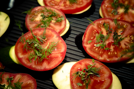 Slices of fresh vegetables on a grill pan surface. Selective focus. Shallow depth of field. Toned. Stock Photo