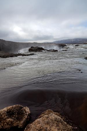 Water of the Godafoss Waterfall - beautiful part of stony rocky desert landscape of Iceland. Lizenzfreie Bilder
