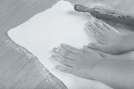 Plump womens hands work with dough on a light wooden table. Toned.