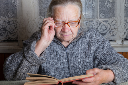 grayness: Elderly woman reads book in rustic interior.