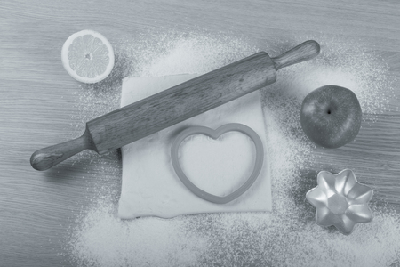 pin board: Set for home baking on a light wooden table with flour. Rolling pin, baking form, dough, half of lemon, apple. Toned.