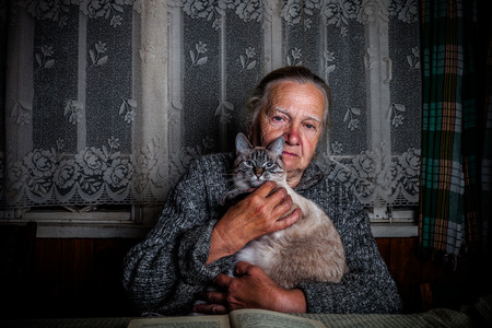 grayness: Elderly woman with cat in rustic interior. Toned.