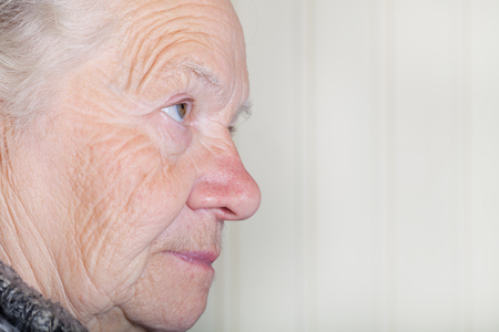 grayness: Portrait of an elderly woman on a light background. Thoughtful profile.
