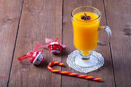 immunity: Glass of sea buckthorn beverage (kissel) on a brown wooden table or board for background. New year theme.