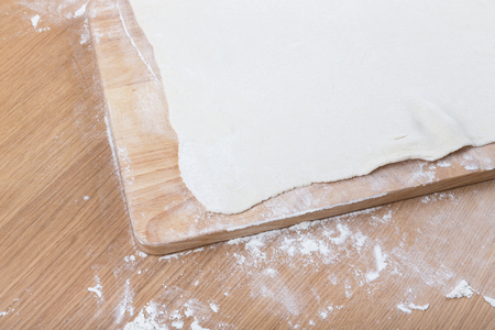 pin board: Puff dough, wooden cutting board on a light table with flour.