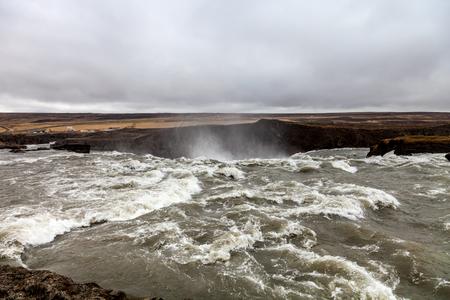 Splashes of the Godafoss Waterfall - beautiful part of stony rocky desert landscape of Iceland.
