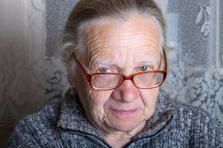 grayness: Elderly woman with glasses in rustic interior.