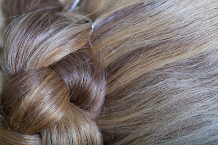 grayness: The hair of an elderly woman is gathered at the back of the head. Close up detail.