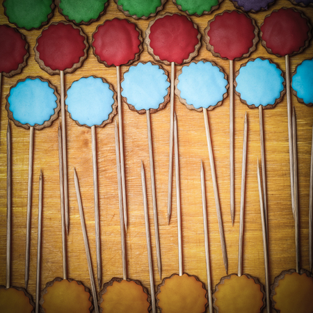Gingerbread cookies with colored mastic on sticks on the old wooden cutting board. Toned.