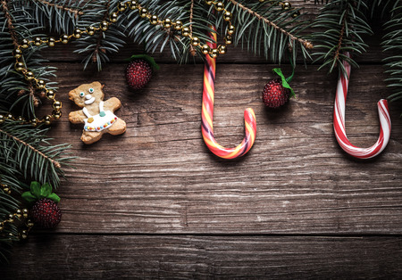 let: Christmas tree branch, candy cane and decorative elements on a wooden table or board for background. New year theme. Space for text. Toned. Stock Photo