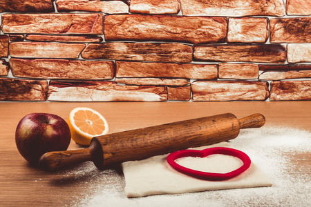 nudelholz: Set for home baking on a light wooden table with flour. Rolling pin, baking form, dough, half of lemon, apple. Toned.