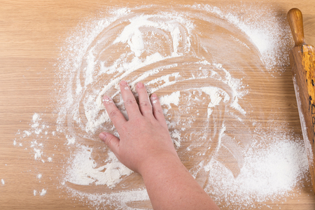 pin board: Plump womens hands work with dough on a light wooden table. Stock Photo