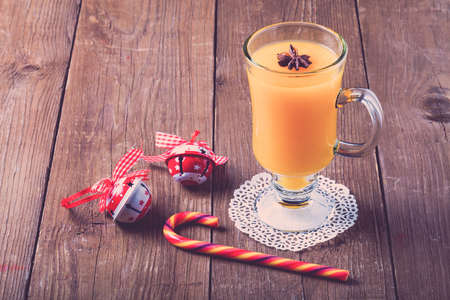 immunity: Glass of sea buckthorn beverage (kissel) on a brown wooden table or board for background. New year theme. Toned.