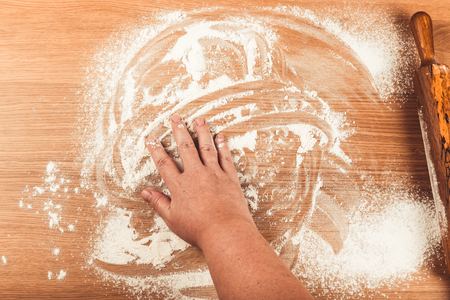 pin board: Plump womens hands work with dough on a light wooden table. Toned.